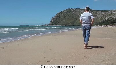 Man Walking On The Beach - Middle-aged Caucasian man walking...