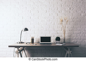 Creative desktop on brick background - Front view of...