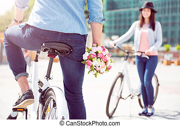 Man sitting on bike and holding flowers - Happy to see her....
