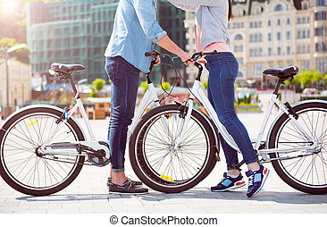 Man and woman standing with bikes