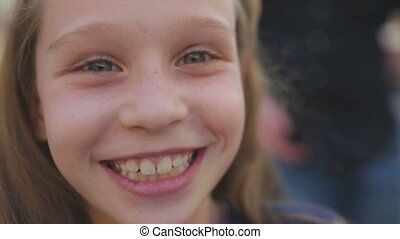 Close up of a young girl smiling as she looks into the camera