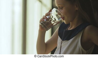 young child enjoys a glass of fresh water