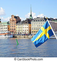 Waterfront in Stockholm and swedish flag. Focus on the...