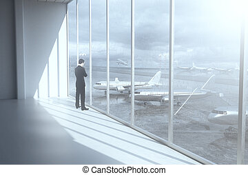 Thoughtful businessman in airport terminal interior with...