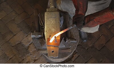 Blacksmith bends a red hot metal billet using a fork. Seen...