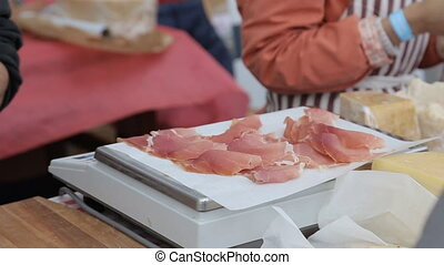Thin slices of pork ham on the wood plate.