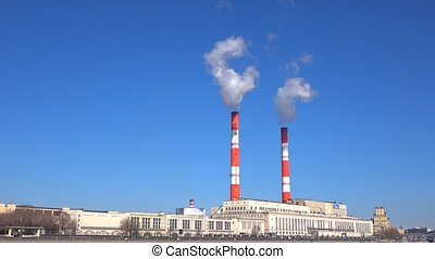 Old heat electric plant and smoke from stacks against blue sky. 4K video
