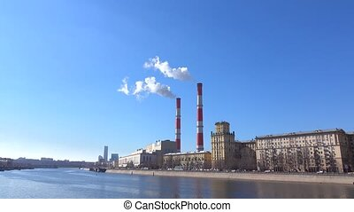 Heat electric plant and smoke from smoke stacks against blue sunny sky. 4K shot