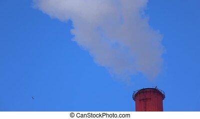 Top of smoking red smoke stack against sunny blue sky. 4K...