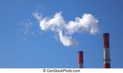 Back lit white smoke and industrial smoke stacks on sunny...