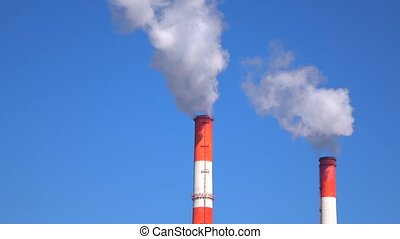 Smoking red and white smoke stacks against sunny blue sky....