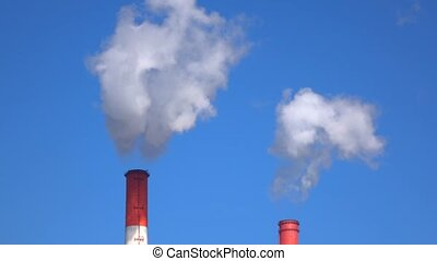 Red smoke stack tops against sunny blue sky. 4K telephoto...