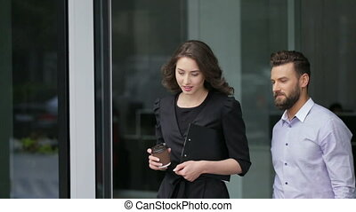 Attractive young businesswoman and her colleague entering...