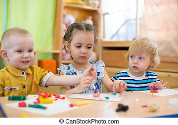 kids doing arts and crafts in day care kindergarten - kids...