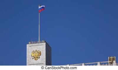 Russian flag and Russian state emblem above government White...