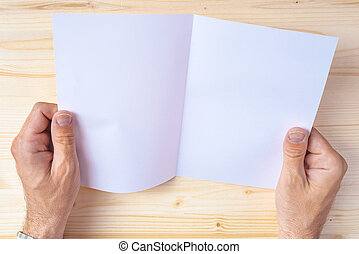 Man holding blank brochure as mock up copy space for graphic...