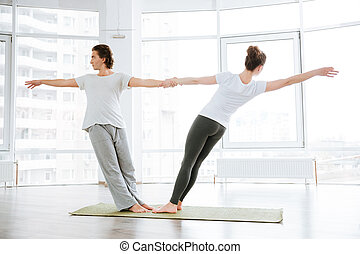 Young couple doing stretching exercises in yoga studio...