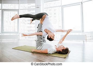 Beautiful couple doing acro yoga exercises in studio...