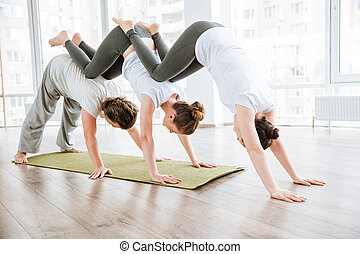 Man and two women practicing acro yoga in group - man and...