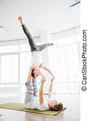 Concentrated couple practicing acro yoga exercises in studio...