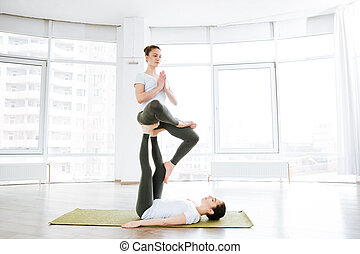 Two pretty young women practicing acro yoga on green mat -...