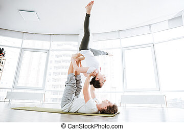 Relaxed young couple balancing and doing acro yoga in studio