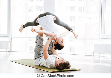 Couple doing flexibility workout in yoga studio - Peaceful...