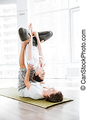 Young couple doing acro yoga in studio together