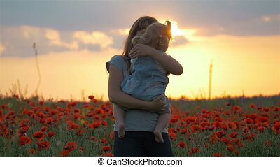 Mother hugs lovely child daughter in poppies field with...
