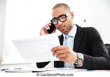 Pensive young businessman looking at documents in office