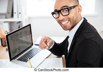 Close-up of smiling smart businessman working with computer...