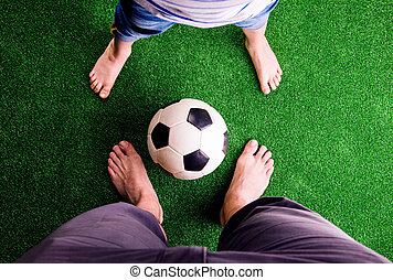 Father and son with soccer ball against green grass - Legs...
