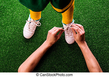 Unrecognizable father tying shoelaces to his son, football -...