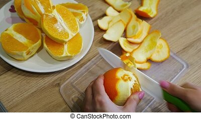 Cutting fresh oranges on a wooden table
