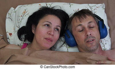 Man Sleeping Earmuffs Woman Talking - Man and woman in bed...