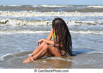 The girl in a yellow bathing suit on the beach. Girl with black hair sitting in sea water head bowed.
