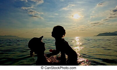 Silhouette of Woman with Toddler in Arms in Sea against Sunset