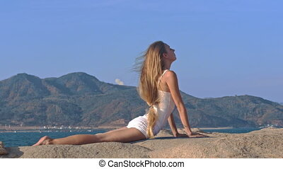 Blond Girl Does Fitness Bends Backward on Large Stone -...