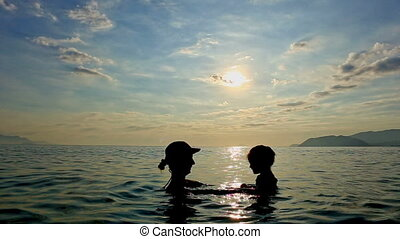Silhouette of Woman with Toddler in Arms in Sea against...
