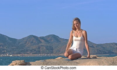 Blond Girl in Top Sits in Lotus Yoga Pose Hands behind Back...