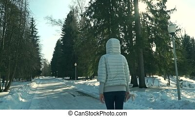 Young sporty woman walks in snowy park on sunny day