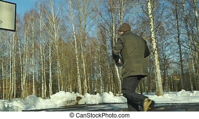 Man playing funny winter basketball with a snowball. Slow motion shot