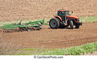 Farm Tractor - Farm tracto preparing the field for planting