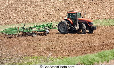 Farm Tractor - Farm tracto preparing the field for planting