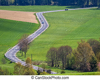 cars on a highway - the band of a main road running through...