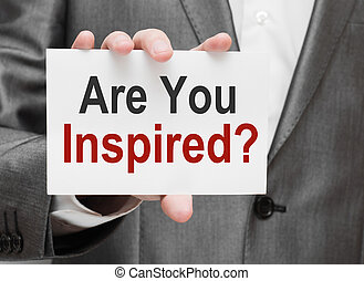 Are You Inspired Written on card in businessmans hands