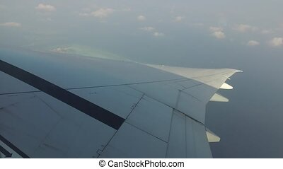 wing of airplane flying in blue sky