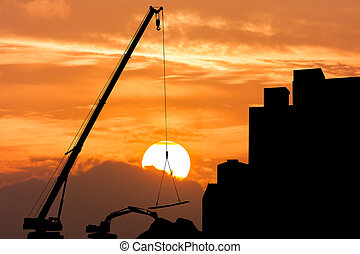 silhouette of excavator and crane working sunset background