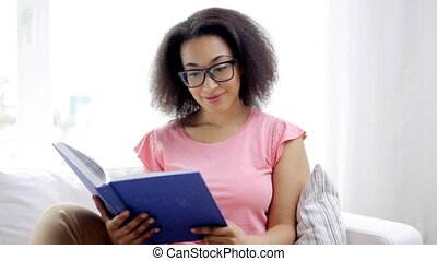 african american young woman reading book at home - leisure,...