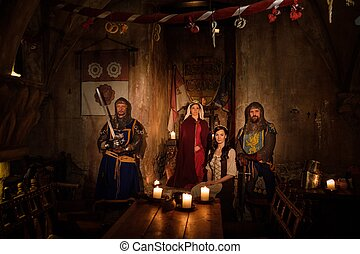 Medieval queen with her courtier and knights on guard in...